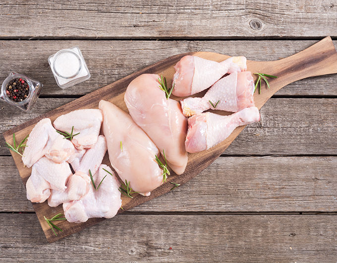 Raw chicken meat on wooden background . Wings , breast and legs